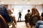 blurred group of people meeting in motivation seminar event at convention hall, speaker raising hand up and audience action follow , cheerful concept