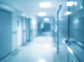 Blurred abstract hospital background - corridor with rooms for patients and bokeh lights (blue filter effect).