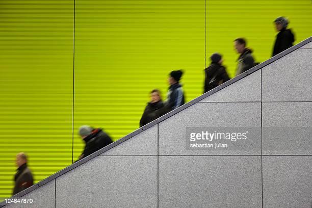Pendler auf Rolltreppe vor grünem Hintergrund und Kopie Raum