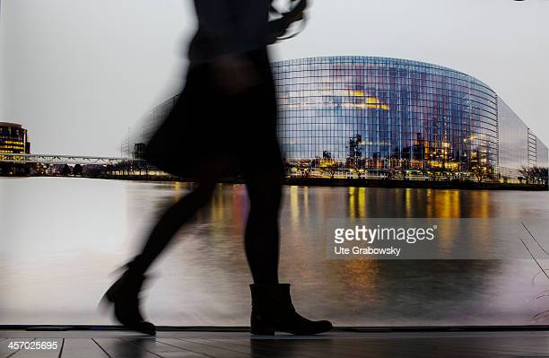 A blurred image of a female visitor walking in front of a large picture of the European Parliament building in Strasbourg at the Parlamentarium...
