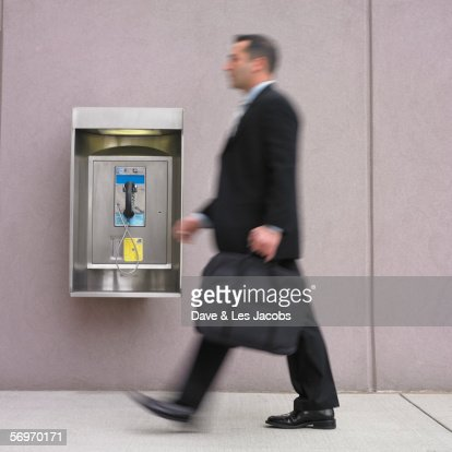 Blurred image of businessman walking by payphone : Stock Photo