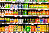 Blurred image of shelf of drink bottles at supermarket