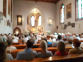 Blurred photo of praying people in the church for abstract background