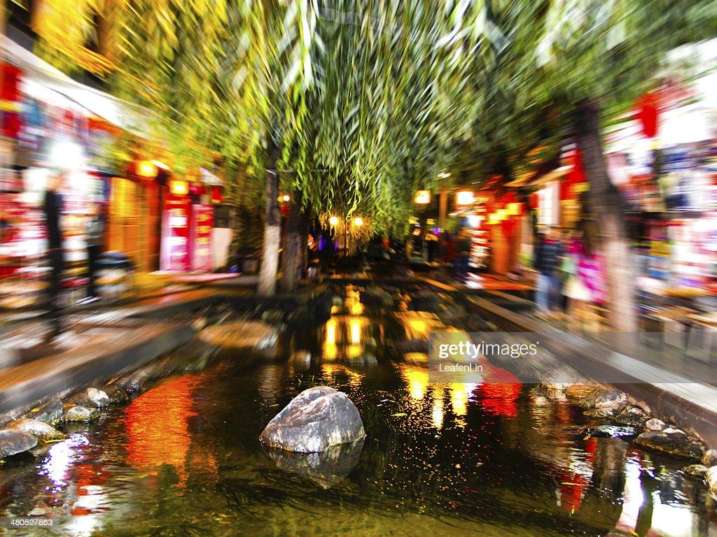 Blurred lights at night ,Lake reflecting the trees and stones : Bildbanksbilder
