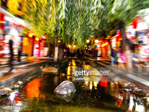 Blurred lights at night ,Lake reflecting the trees and stones : Stockfoto