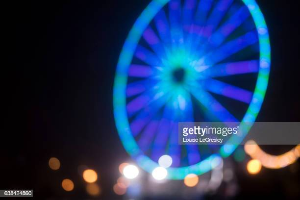 Blurred lights of a ferris wheel photographed at night