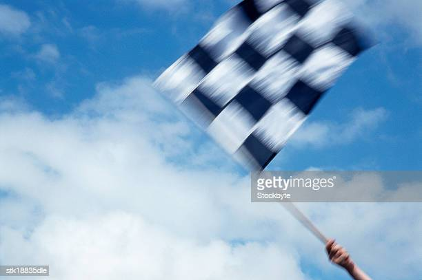 blurred low angle view of a checkered racing flag
