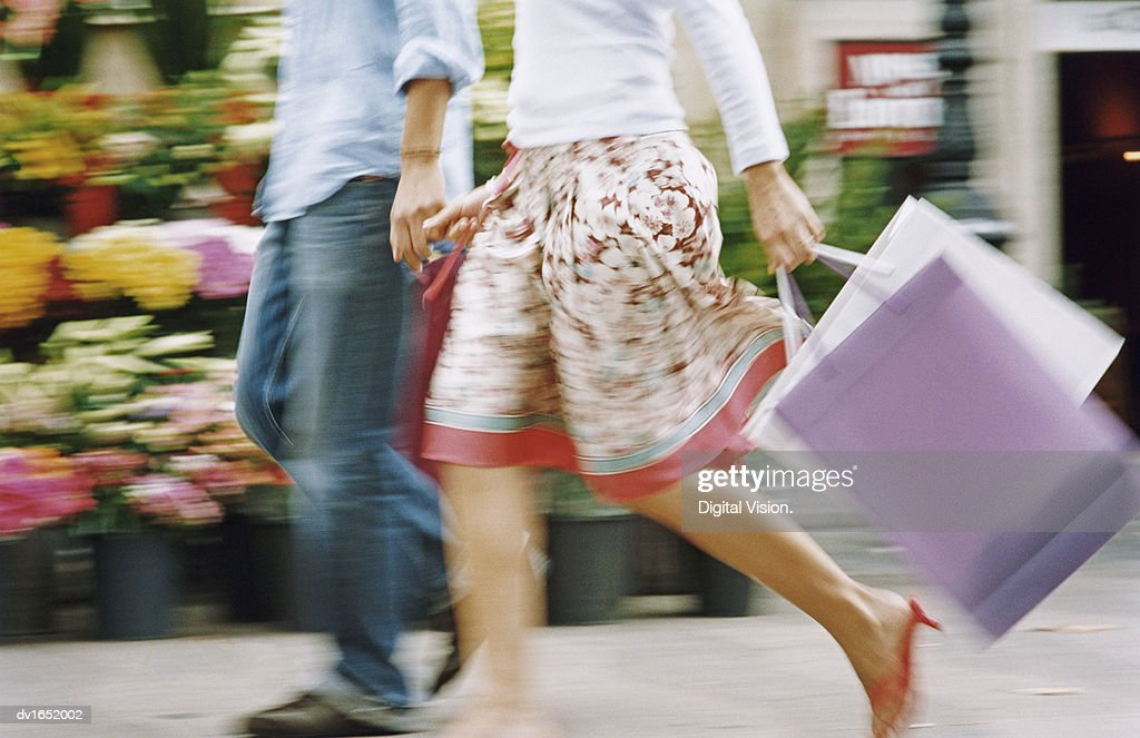 Blurred Low Section Image of a Couple Walking Down the Street Holding Hands and Carrying Shopping Bags : Stock Photo