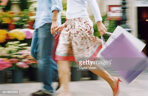 Blurred Low Section Image of a Couple Walking Down the Street Holding Hands and Carrying Shopping Bags : Bildbanksbilder