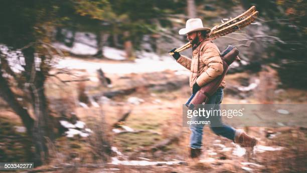 Blurred motion as man carries camping gear through woods