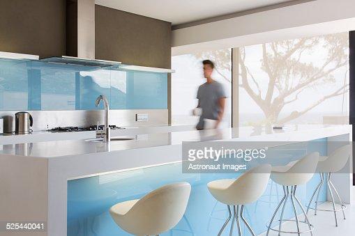 Blurred motion man walking through white and blue modern kitchen