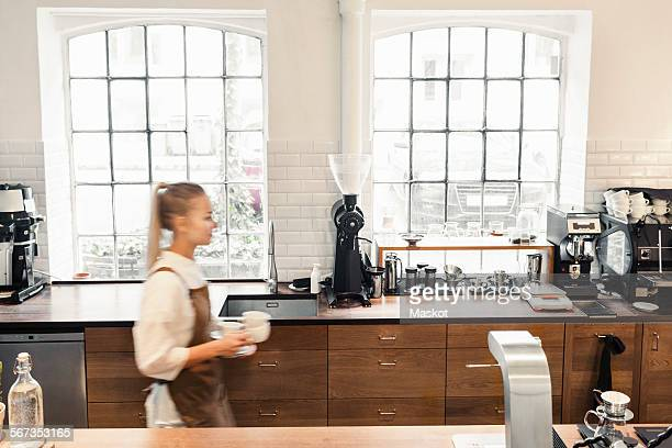Blurred motion of barista walking at cafe