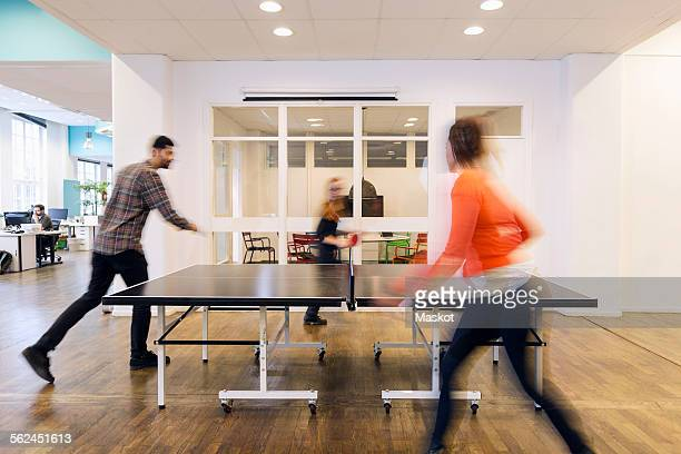 Blurred motion of business people playing table tennis in creative office