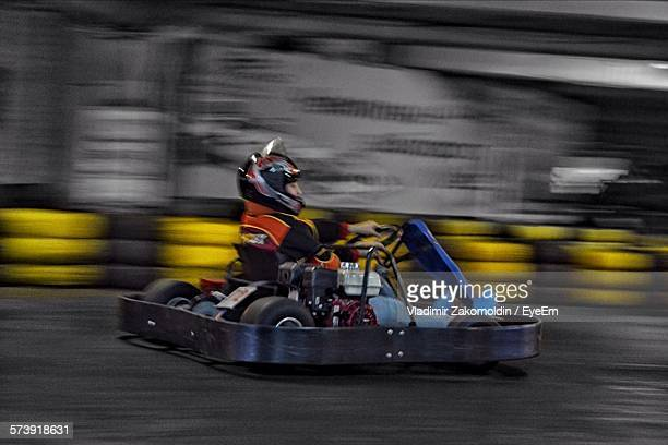 Blurred Motion Of Man Go-Carting During Race