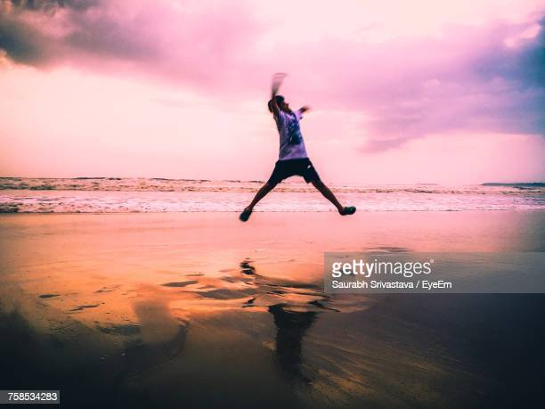 Blurred Motion Of Man Jumping On Shore At Beach During Sunset