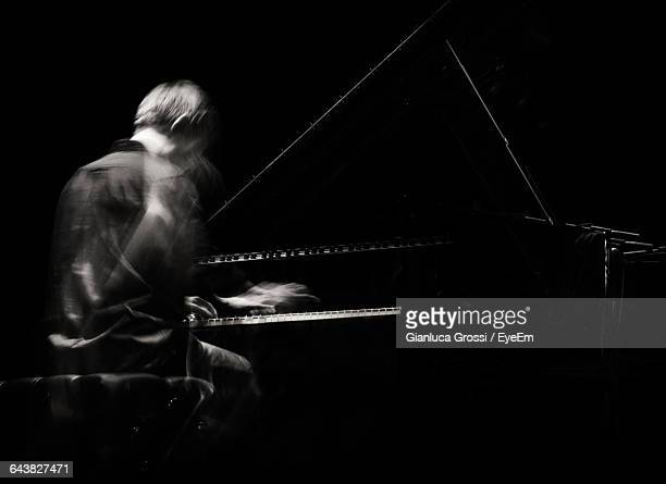 Blurred Motion Of Man Playing Piano Against Black Background