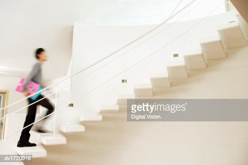 Blurred Motion Shot of a Man Ascending a Stairway in a Modern Home : Stock Photo