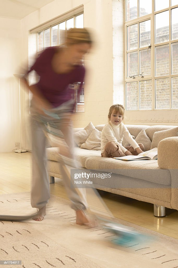 Blurred Motion Shot of a Woman Using a Vacuum Cleaner While Her Young Daughter is Sitting on a Sofa : Stock Photo