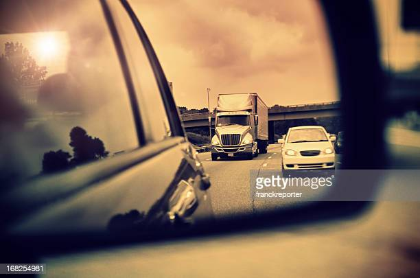 Mouvement flou vue dans le miroir latéral voiture au coucher du soleil