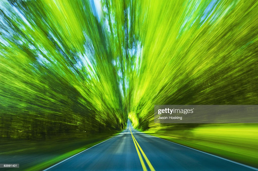 Blurred motion view of road and trees