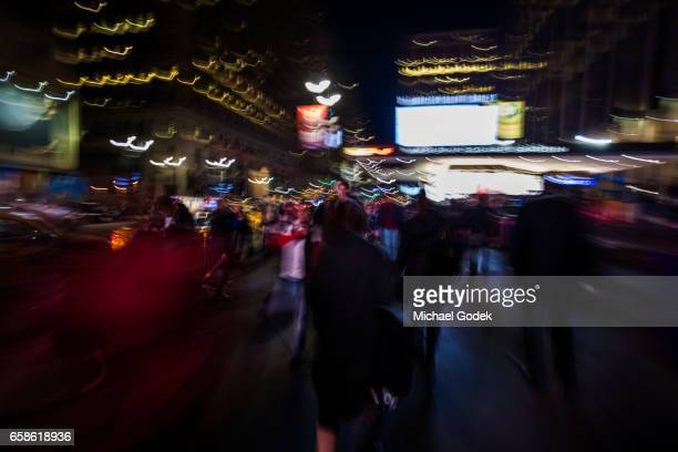 Blurred motion walking through a crowd near Madison Square Garden at night in New York City