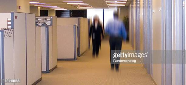Blurred office workers walking down a corridor with cabinets