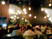 Blurred people drinking at the bar with bokeh light background