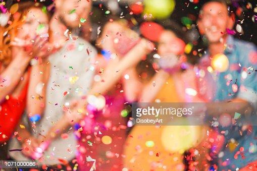 Partido haciendo borrosa de la gente tirando confeti - jóvenes celebrando el fin de semana noche - entretenimiento, diversión, fin de año, vida nocturna y fiesta concepto - desenfocada foto : Foto de stock