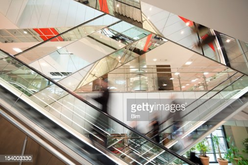 Blurred People on Escalator in Modern Glass Interior
