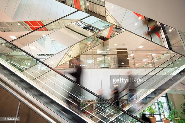 Blurred People on Escalator in Modern Glass Interior