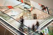 Blurred People on Escalator in Modern Interior