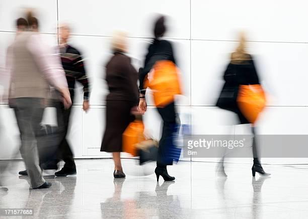 Blurred People Rushing Down Corridor, Women Carrying Shopping Bags