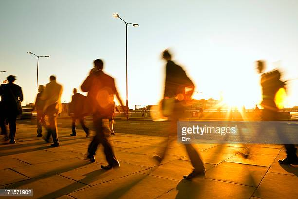 Blurred people walking in sunset light