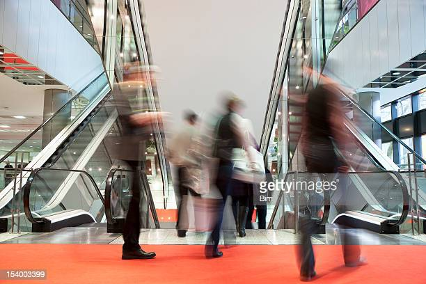 Blurred People Walking Red Carpet Towards Escalators in Modern Interior