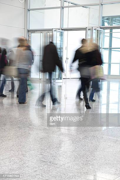 Blurred People Walking Through Glass Doors