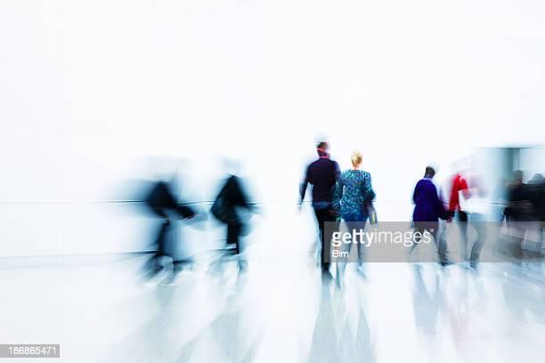 Blurred people walking toward a door in a hallway