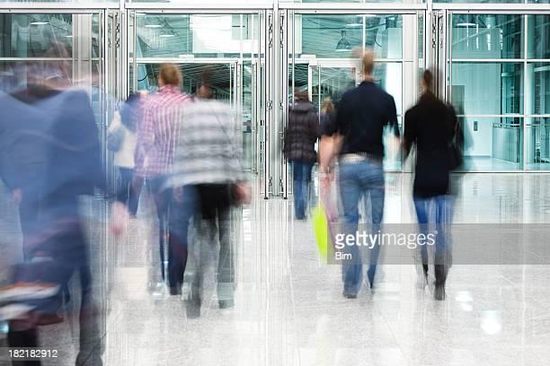 Blurred People Walking Toward Glass Doorway