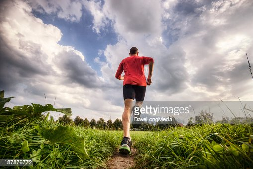 Blurred photo of a runner training in a green surrounding