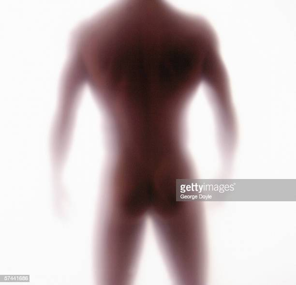 blurred rear view of a nude man standing