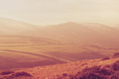 Blurred background of fields, hills, and mountains. Designed to work with text overlays including the text colour white. Artistic intent with filters and desaturation.