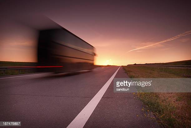 Blurred semi-truck on highway in the sunset