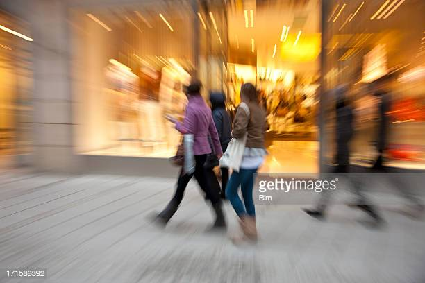 Blurred Shoppers Passing by Illuminated Shop Window at Dusk