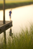 Blurred shot of a child standing on the edge of a floating dock with marsh grasses in the foreground