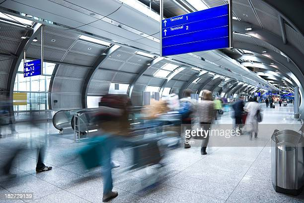 Blurred Travellers Walking Through Airport Tunnel