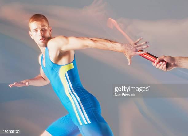 Verschwommene Blick auf den Athleten übergeben baton