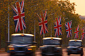A blurred view of black London taxi cabs driving along The Mall at dusk.