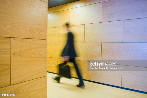 Blurred view of Caucasian businessman walking in office hallway