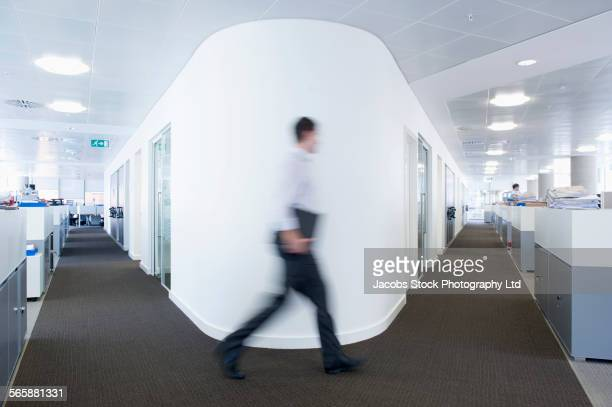 Blurred view of Caucasian businessman walking in office