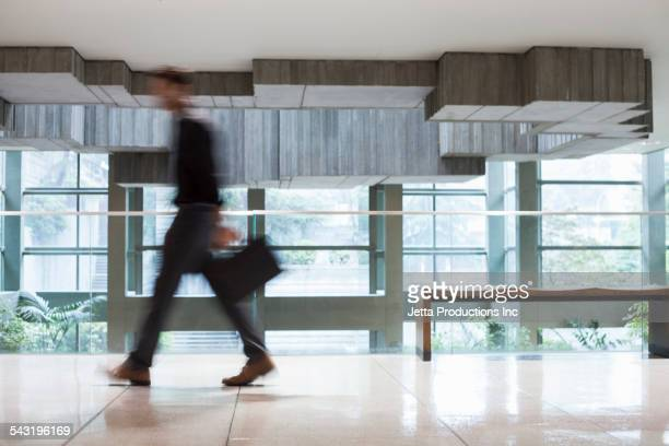 Blurred view of Caucasian businessman walking on office balcony