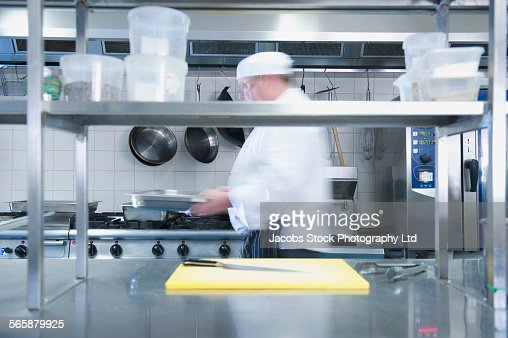 Restaurant Kitchen View caucasian chef tasting food in restaurant kitchen stock photo